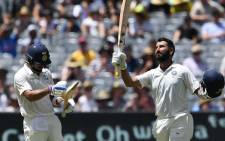 India's batsman Cheteshwar Pujara (R) celebrates reaching his century (100 runs) with team's captain Virat Kohli during day two of the third cricket Test match between Australia and India in Melbourne on 27 December 2018. Picture: AFP