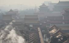 FILE: Steam rises behind a wall of the Forbidden City, once the home of China's emperors, on a polluted day in Beijing in December 2015. Picture: AFP.