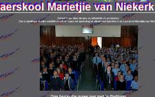 This screengrab of the Laerskool Marietjie van Niekerk website shows what appears to be an old South African flag in the school hall.