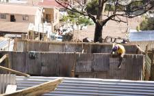 A Mandela Park resident carefully hammers a nail into the structure he is erecting. Picture: Cindy Archillies/EWN
