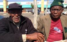 Pensioners sit just metres away from the crime scene where nine elderly people and two security guards were shot during an armed robbery. Picture: Vumani Mkhize/EWN.