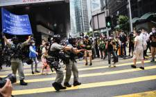 Hong Kong riot police (L) issue a warning as they plan to clear away people gathered in the Central district of downtown Hong Kong on May 27, 2020, as the city's legislature debates over a law that bans insulting China's national anthem. Picture: AFP.