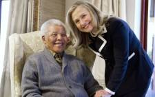 US Secretary of State Hillary Clinton stands next to a Mr Nelson Mandela statue.