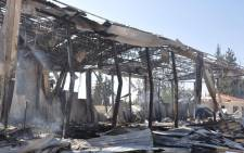 A small fire smolders (L) at the site of an attack on the pro-government Al-Ikhbariya satellite television channel's offices outside Damascus. Picture: AFP.