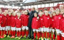 Russian President Vladimir Putin talks to young football players during a visit to Spartak's stadium Otkritye Arena in Moscow, on 27 August 2014. Picture: AFP.