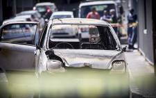 Police and forensic crews examine the scene of the burnt out shell of the car that was allegedly petrol bombed in Wesley Street, Gardens. Picture: Thomas Holder/EWN