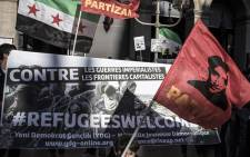 """People hold the Syrian Independence flag, the flag used by the Syrian National Coalition and Syrian Interim Government and a banner reading """"Against imperialist wars and capitalist borders #Refugeeswelcome"""" on September 6, 2015 during a rally in support of Syrian refugees at the place de la Comedie in Lyon. Picture: AFP."""