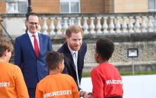 FILE: Britain's Prince Harry, Duke of Sussex gestures as he chats to school children prior to the draw for the Rugby League World Cup 2021 at Buckingham Palace in London on 16 January 2020. Picture: AFP