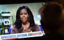 FILE: A person watches former First Lady Michelle Obama speak during the opening night of the Democratic National Convention, being held virtually amid the novel coronavirus pandemic, in Los Angeles, on 17 August 2020. Picture: AFP