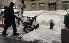 FILE: A man clears snow off the streets of New York following a blizzard that swept across the northeastern United States. Picture: Annwen Quilliam.