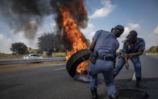 Police clear a burning tyre off The Golden Highway, set alight by protesters in Eldorado Park and Freedom Park who are protesting over service delivery. Picture: Thomas Holder/EWN.