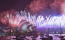 New Year's Eve fireworks erupt over Sydney's iconic Harbour Bridge and Opera House (L) during the fireworks show on 1 January 2020. Picture: AFP