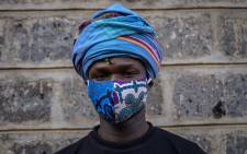 """Kenyan fashion designer of """"Lookslikeavido"""", David Avido, 24, poses for a portrait at his studio in Kibera, Nairobi with a mask he made, that he creates from remnant of cloth he uses, to hand out to people for free so that they can wear it as a preventive measure against the coronavirus. Picture: AFP."""