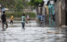 People are seen walking in flooded streets, in a neighbourhood of the commune of Cite Soleil, in the Haitian Capital Port-au-Prince, on 4 October, 2016. Picture: AFP.