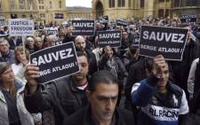 "Protesters hold signs reading ""Save Serge Atlaoui"" on 25 April, 2015 during a rally near the city hall and cathedral of Metz, eastern France, in support of French national Serge Atlaoui, on death row in Indonesia for drug trafficking. Picture: AFP."