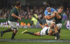 South Africa's tighthead prop Frans Malherbe (L) looks on as Argentina's flanker Pablo Matera (2R) is tackled by South Africa's inside centre Andre Esterhuizen(R) and full-back Willem le Roux (C) during The Rugby Championship rugby union match between South Africa and Argentina at Johnson Kings Park Stadium in Durban on 18 August 2018.