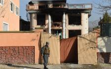 An Afghan policeman keeps watch at the gate of a foreign compound following an attack by Taliban militants in Kabul on 30 November, 2014. Picture: AFP.