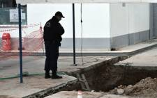 A policeman looks at the hole where an unexploded bomb dating to the World War II was found during work to expand a gas station's underground tanks in Thessaloniki. Picture: AFP.