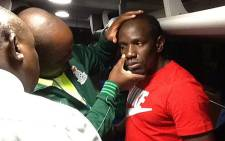 Safa President Kirsten Nemantandani (back to camera) checks Zambian soccer player Kennedy Mweene's injuries after the team bus was stoned after leaving the FNB stadium. Picture: Facebook.
