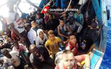 This image grab taken from a handout video and released by the Italian coastguard (Guardia Costiera) on 30 August 2016, shows migrants on a boat in the Mediterranean Sea during a rescue operation. Picture: AFP.
