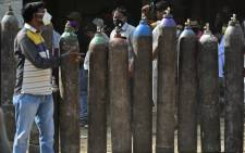 People wait to refill their medical oxygen cylinders for Covid-19 coronavirus patients at an oxygen refilling station in Allahabad on 24 April 2021. Picture: AFP