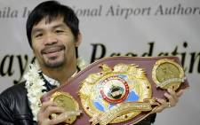 This file photo taken on April 14, 2016 shows Filipino boxer Manny Pacquiao holding his championship belt as he arrives at Manila International Airport in Manila. Picture: AFP