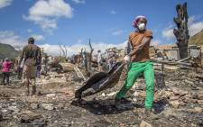 Residents of the Imizamo Yethu informal settlement in Hout Bay, Cape Town, help to clear the rubble on 28 December 2015 after a fire ripped through a section. Picture: Aletta Harrison/EWN
