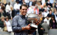 FILE: Spain's Rafael Nadal bites the Mousquetaires Cup (The Musketeers) as he poses at the end of the men's singles final match against Austria's Dominic Thiem on day fifteen of The Roland Garros 2019 French Open tennis tournament in Paris on 9 June 2019. Picture: AFP