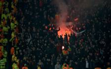 Flares are lit by the Liverpool supporters during the Uefa Europa League round of 16, second leg football match between Manchester United and Liverpool at Old Trafford in Manchester, North West England on 17 March, 2016. The game ended 1-1, Liverpool going through 3-1 on aggregate. Picture: AFP.
