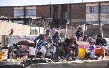Residents from a Claremont informal settlement sit with belongings they managed to save after a fire. Picture: Kayleen Morgan/EWN