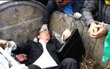 A screengrab of Vitaly Zhuravsky being thrown into a trash bin by angry protesters in Ukraine on 16 September, 2014.