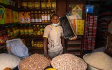 Paul Chinedu poses for a portrait in his shop in a market at Illaje Bariga, Lagos on June 29, 2021. Since the start of the pandemic in 2019, food prices have risen by an average of more than 22%, according to official statistics, and feeding a family properly has become a daily challenge.  Picture: Benson Ibeabuchi / AFP