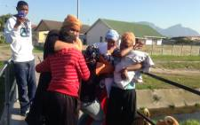 Residents in the Grassy Park area have gathered at the scene where the body of three-year-old Olivia van Voeght was found. Picture: Lauren Isaacs/EWN