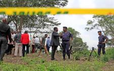 Members of the KwaZulu-Natal provincial executive council and the South African Police Services visit the site of a suspected mass burial site discovered at Glenroy Farm. Picture: AFP.