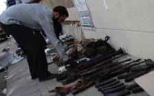A Pakistani investigator inspects weapons seized from militants following an assault by militants at Karachi airport in Karachi on 9 June 2014. Picture: AFP.