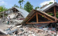 An Indonesian man examines the remains of houses, after a 6.4 magnitude earthquake struck, in Lombok on July 29, 2018. A powerful earthquake on the Indonesian tourist island of Lombok killed at least 10 people, injured dozens and damaged hundreds of homes. Picture: AFP