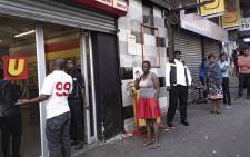 People queue at a grocery store in Hillbrow on the first day of the coronavirus lockdown on 27 March 2020. Picture: Sethembiso Zulu/EWN