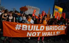 "Demonstrators hold a banner reading ""Build bridges not walls!"" as they gather at Berlin's Alexanderplatz during a major demonstration for an open and caring society organised by the action group ""Unteilbar"" (indivisible) on 13 October 2018. Picture: AFP."