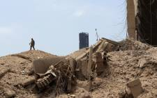 FILE: A soldier stands atop rubble at the devastated site of the explosion in the port of Beirut on 6 August 2020 two days after a massive explosion devastated the Lebanese capital in a disaster that has sparked grief and fury. Picture: AFP