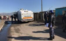Police monitoring the situation in Phumlani Village amid protests by residents against the lack of housing and service delivery. Picture: Monique Mortlock/EWN.