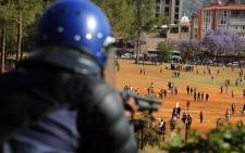 FILE: A police officer gets ready to fire rubber bullets as the crowd of students disperse during protests over proposed university fee increases at the Union Buildings in Pretoria on 23 October 2015. Picture: Reinart Toerien/EWN