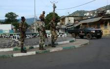 "Soldiers from the Comoros armed forces station and wait outside the ""Medina"" at Mutsamudu on 19 October, 2018 in Anjouan, Comoros. Picture: AFP"