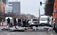 Rescuers and police officers work around a car after a blast caused by an explosive device killed its driver travelling down a street in central Berlin on March 15, 2016. The blast occurred during peak-hour traffic on Bismarckstrasse, within sight of the Victory Column monument, leaving the front of the car severely dented after it flipped over, while debris was strewn a few metres away. Picture: AFP.
