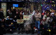 "Doña Manolita Lottery Administration shop employees celebrate having sold the winning number 26590, that represents takings of €4 million (£2.9 million) of Spain's Christmas lottery named ""El Gordo"" (Fat One) in Madrid on 22 December 2019. Picture: AFP"