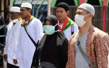 Pilgrims from Asia wear nose and mouth masks on a street of the holy city of Mecca in Saudi Arabia  on 24 September, 2014. Picture: AFP.