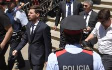 This file photo taken on 2 June 2016 shows Barcelona's football star Lionel Messi (L) leaving the courthouse in Barcelona. Picture: Lluis Gene/AFP.