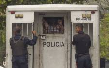 Police agents transport surviving prisoners after police holding cells caught fire in Valencia, northern Carabobo state, Venezuela, on 29 March 2018. Picture: AFP.