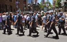 Police walk through Martin Place as spectators look on during a hostage siege in the central business district of Sydney on December 15, 2014. Picture: AFP.