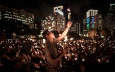 FILE: A man takes a picture with his mobile phone as people hold candles to commemorate Chinas 1989 Tiananmen Square events during a candlelight vigil in Hong Kong. Picture: AFP
