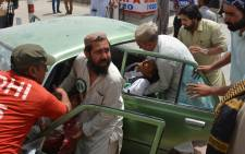 Pakistani men transport injured blast victims at a hospital after a suicide attack near a polling station in Quetta on 25 July, 2018. Picture: AFP